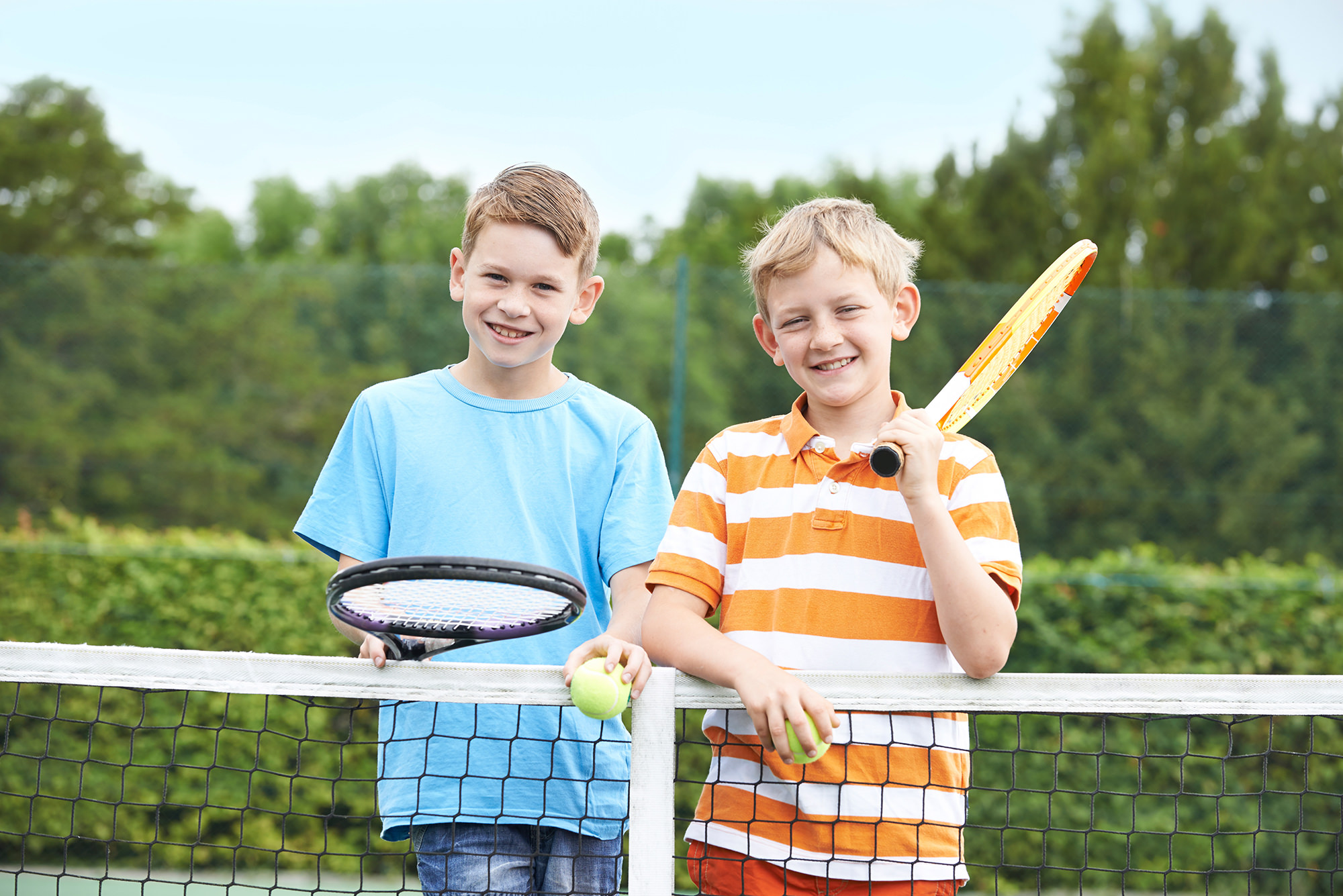 Portrait Of Two Boys Playing Tennis Together